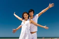 Couple som tycker om frihet på stranden Royaltyfri Bild
