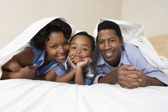 Couple With Son Lying Underneath Sheet. Portrait of an African American couple with son lying underneath sheet royalty free stock images