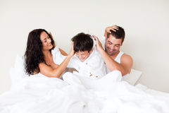 Couple and son playing in bed Royalty Free Stock Image