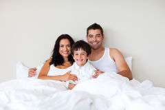 Couple and son together in bed smiling royalty free stock photo