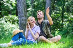 Couple soulmates at romantic date. Romantic couple students enjoy leisure looking upwards observing nature background. Romantic date at green meadow. Couple in royalty free stock photography