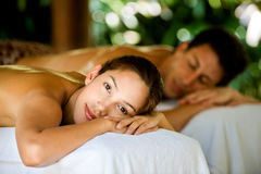 Couple At Spa. An attractive young couple lying on massage beds at a spa outdoors Royalty Free Stock Image