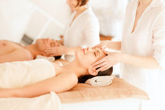 Couple in spa. Health and beauty, resort and relaxation concept - couple in spa salon getting facial massage Royalty Free Stock Images