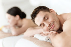 Couple in spa. Health and beauty, resort and relaxation concept - couple in spa salon lying on the massage desks Royalty Free Stock Image