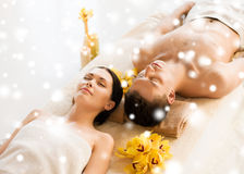 Couple in spa salon lying on the massage desks Stock Photos