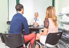 Couple speaking with doctor. Doctor talking with his patients in a clinic studio - Couple with health problem in hospital receive prognosis from doctor Stock Photos