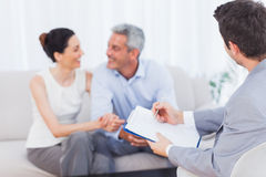 Couple speaking while salesman is holding contract. On couch at home royalty free stock photos