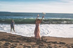 Couple spend a fun time at the beach playing with flying plate Stock Photography