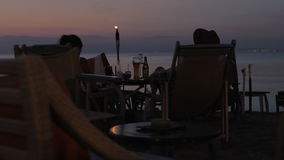 Couple spending evening in cafe on the beach stock video