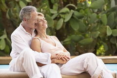 Couple Spending Romantic Time By Pool. Happy middle aged couple spending romantic time by pool Royalty Free Stock Photo