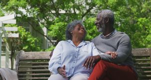 Couple spending time together in the garden. Front view of senior African American couple with white hairs in the garden, sitting on a bench, embracing and