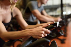 Couple in a spinning class wearing sportswear. Two people biking in the gym, exercising legs doing cardio workout cycling bikes. Couple in a spinning class Royalty Free Stock Images