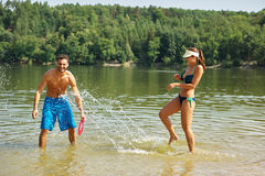 Couple splashes and sprays each other with water Royalty Free Stock Image
