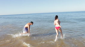 Couple Splashing One Another In Sea. Couple run into sea before splashing one another.Shot on Canon 5d Mk2 with a frame rate of 30fps stock video footage