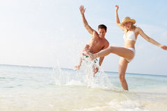 Couple Splashing In Sea On Beach Holiday Royalty Free Stock Photography