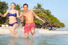 Couple Splashing In Sea On Tropical Beach Holiday Royalty Free Stock Photo