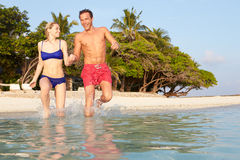 Couple Splashing In Sea On Tropical Beach Holiday Royalty Free Stock Images