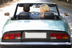 Couple in sports car. Smiling at each other Stock Photography