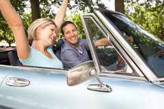 Couple in sports car. Smiling and putting hands in the air Stock Image