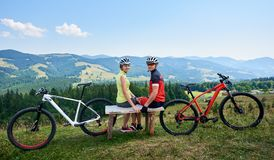 Couple sportsman cyclists sitting on wooden bench near bicycles, looking to the camera Stock Image