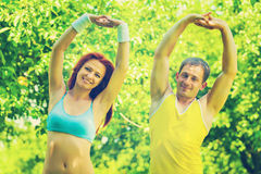 Couple sportsman and sportswoman exercising in a park field inst Royalty Free Stock Photos