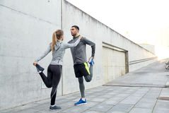 Couple of sportsmen stretching leg on city street. Fitness, sport, training and lifestyle concept - couple of sportsmen stretching leg on city street Royalty Free Stock Images