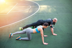 Couple in sportswear doing plank position on the stadium stock images