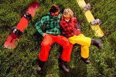 Couple in sportswear with snowboards lying on the grass Stock Image