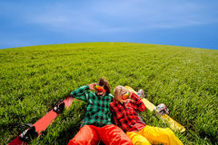 Couple in sportswear with snowboards lying on the grass Royalty Free Stock Photography