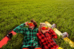 Couple in sportswear with snowboards lying on the grass Royalty Free Stock Images