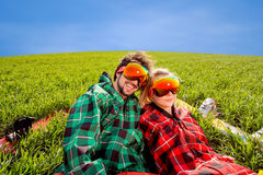 Couple in sportswear with snowboards lying on the grass Stock Photo