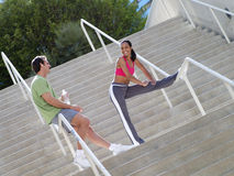 Couple, in sportswear, warming down from jog, man leaning against railing on steps, woman stretching leg (tilt) Stock Image