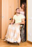 Couple with spouse in wheelchair near door Stock Photos