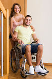 Couple with spouse in wheelchair near door Royalty Free Stock Photos