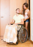 Couple with spouse in wheelchair near door Stock Photo