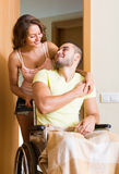 Couple with spouse in wheelchair near door Stock Images