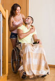 Couple with spouse in wheelchair near door Royalty Free Stock Images