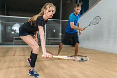 Couple with squash rackets, indoor training club. Young couple with squash rackets, indoor training club. Active sport lifestyle. Recreation workout, match with Stock Photography