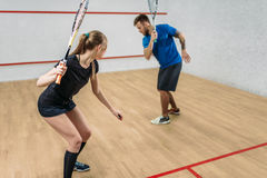 Couple with squash rackets, indoor training club. Young couple with squash rackets, indoor training club. Active sport lifestyle. Recreation workout, match with Royalty Free Stock Images