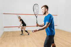 Couple with squash rackets, indoor training club. Young couple with squash rackets, indoor training club. Active sport lifestyle. Recreation workout, match with Stock Images