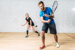 Couple with squash rackets, indoor training club stock photography