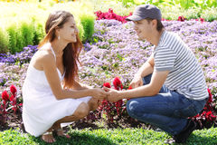 Couple squatted down at flower-bed Stock Photos