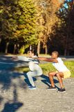 couple squatting in park stock images