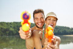 Couple with squirt guns laughing happily Stock Photography