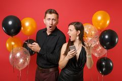 Couple stand back to back messaging in cellphone celebrating birthday holiday party on red background air