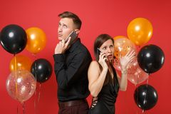 Couple stand back to back talking on cellphone celebrating birthday holiday party isolated on red background air