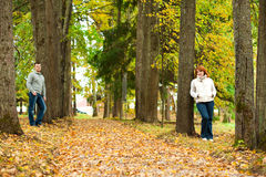 Couple stand leaning against a tree Stock Image