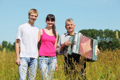 Couple stand near grandfather with accordion. In field near wood stock illustration