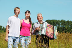 Couple stand near grandfather with accordion. In field near wood, close eyes royalty free illustration