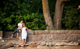 Couple stand next stonewall in forest Stock Photography